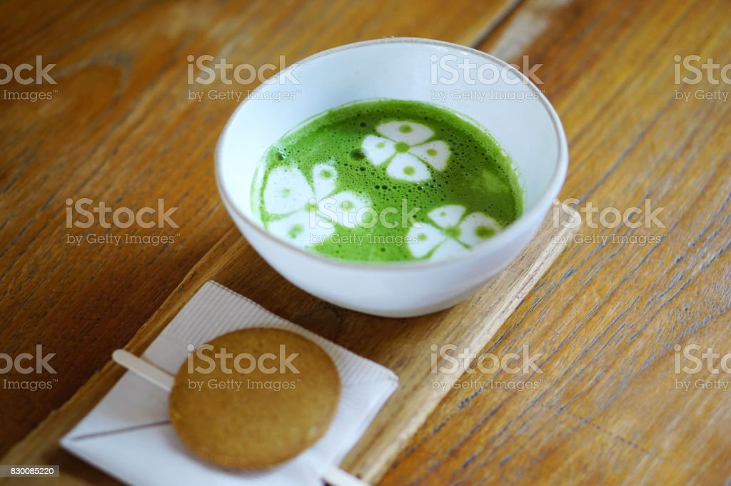 A cup of Hot Matcha with latte art or Green Tea with milk, served with cookie on wooden table, The traditional Chinese and Japanese drink. stock photo