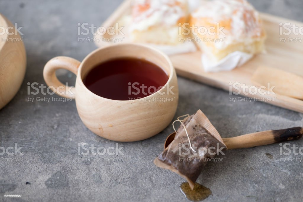 Cup of hot tea and bun with icing for breakfast stock photo