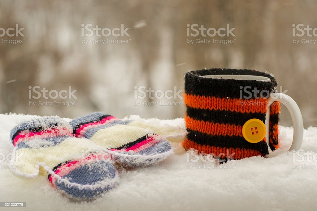 Cup of hot tea and mittens in the snow stock photo