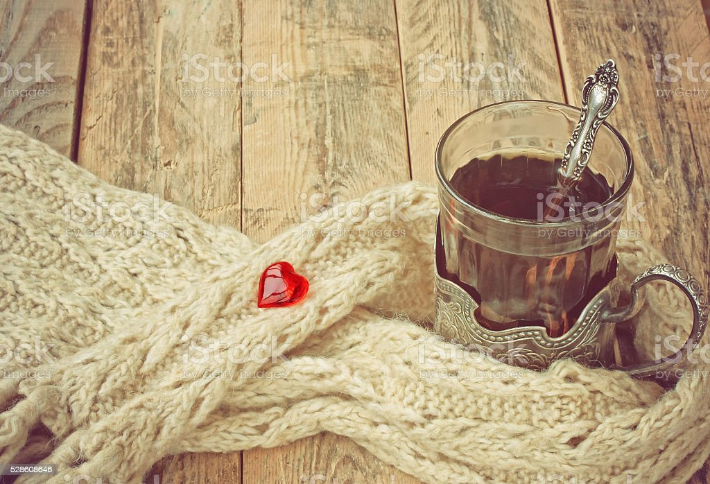 cup of hot tea in cup holder, scarf, red heart stock photo