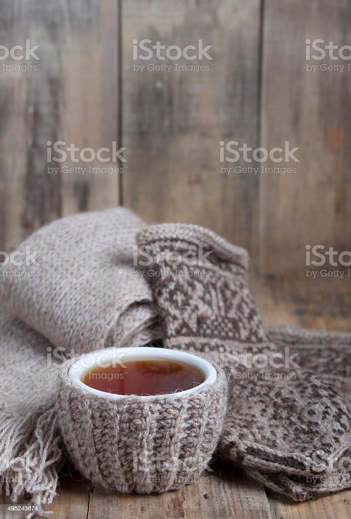 Cup of hot tea , scarf and gloves with ornament. stock photo