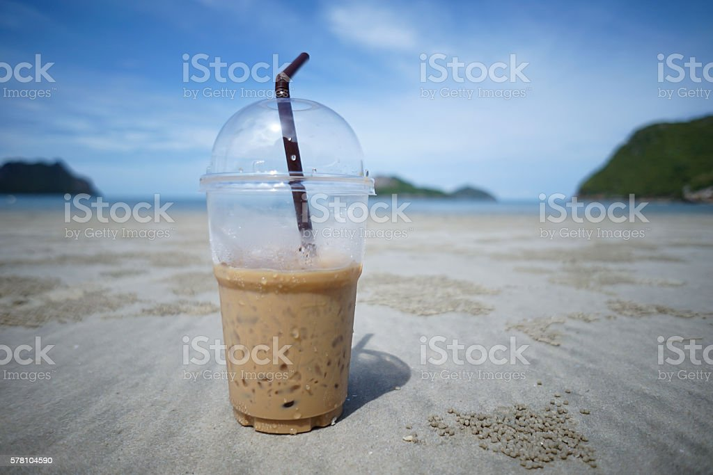 cup of iced coffee on a sand with blur sea stock photo