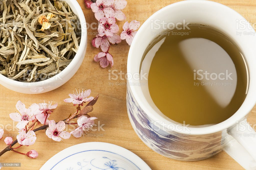 Cup of Jasmine tea with tea leaves and pink blossom royalty-free stock photo