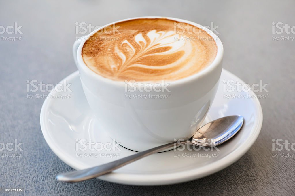 Cup of latte coffee and spoon on gray counter stock photo