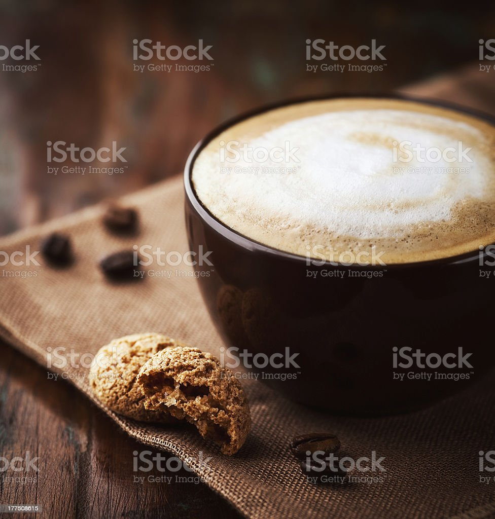 A cup of latte filled to the brim with white and brown foam  royalty-free stock photo