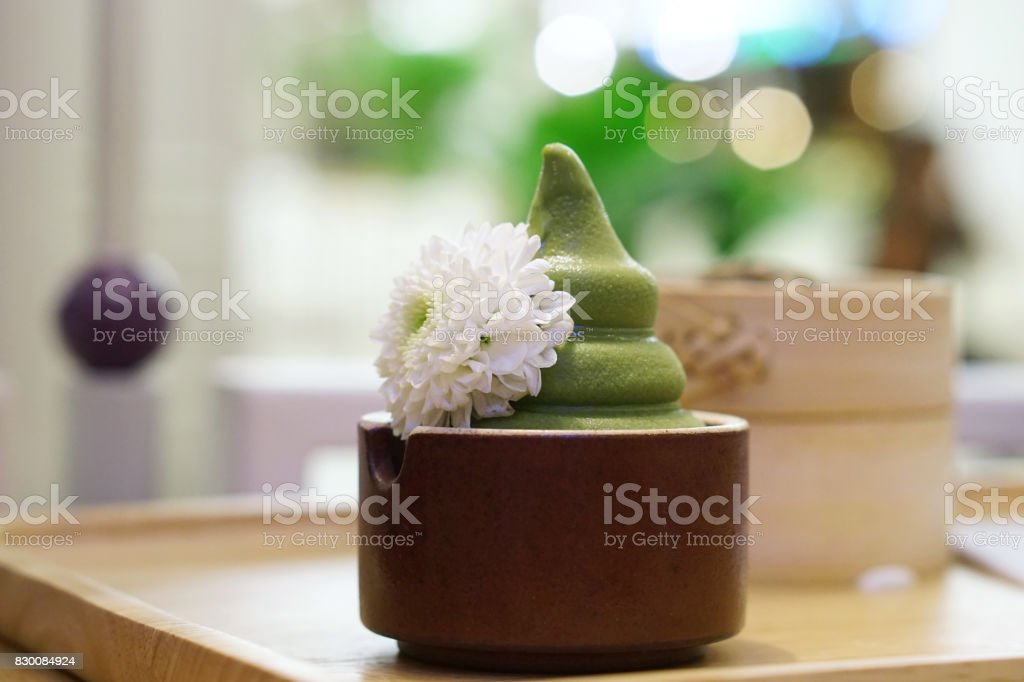 A cup of matcha green tea soft serve or ice cream, decorated with flower. stock photo