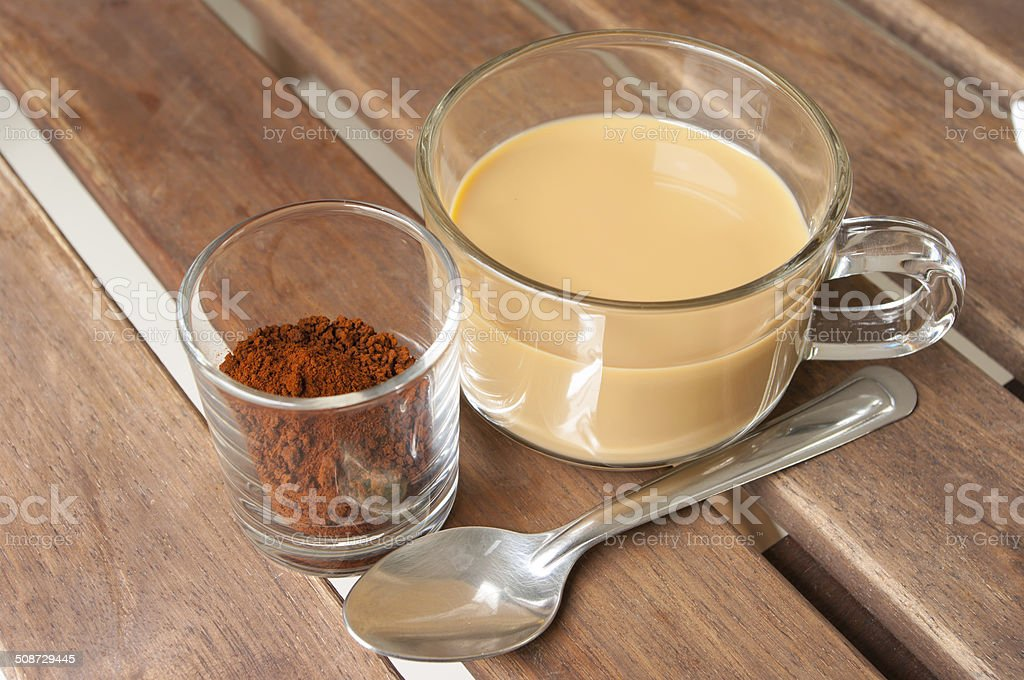 cup of milk coffee and coffee powder on wooden table stock photo