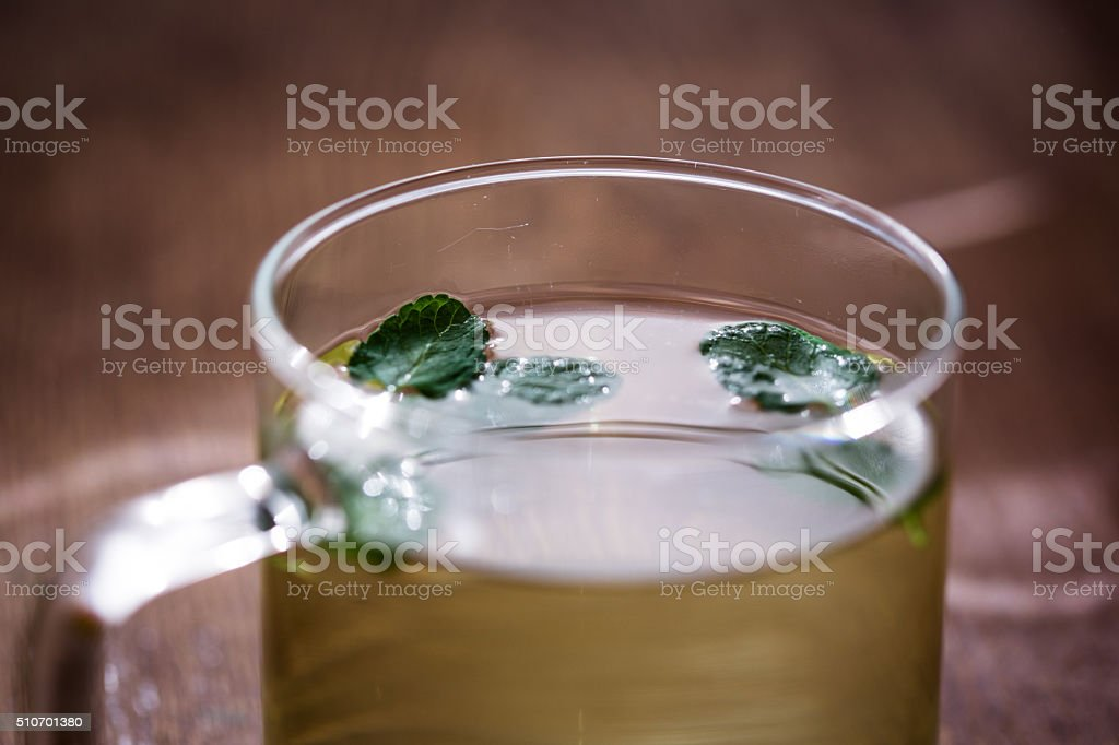 Cup of mint tea in glass teacup, close up stock photo