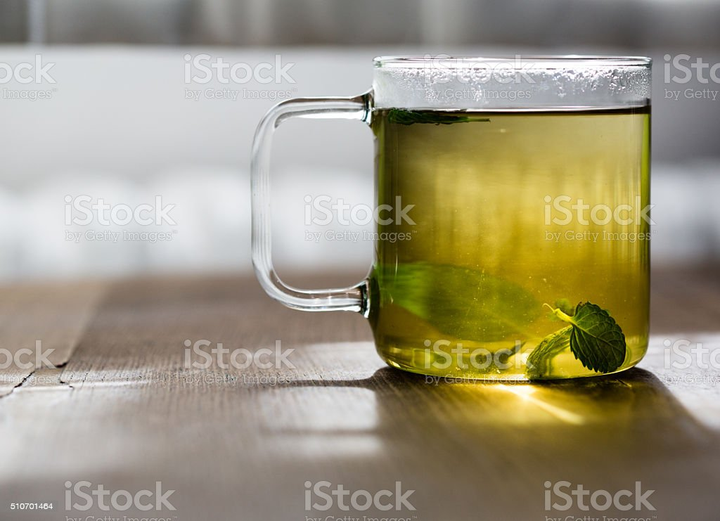 Cup of mint tea in glass teacup stock photo