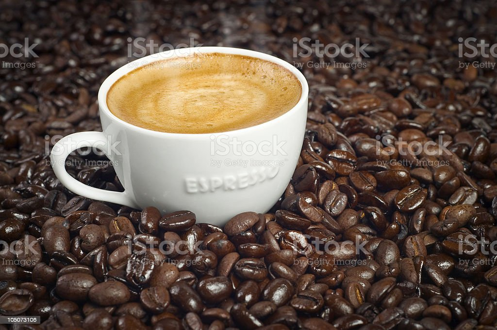 Cup of morning espresso in a pile of coffee beans royalty-free stock photo