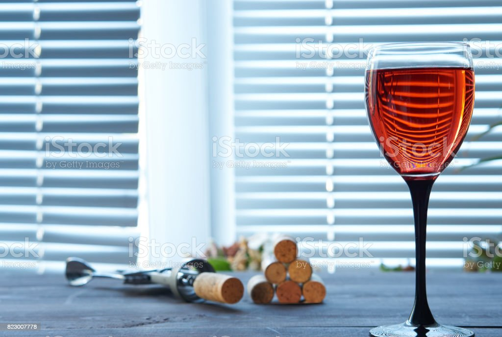 cup of pink wine on table with corkscrew and corks stock photo