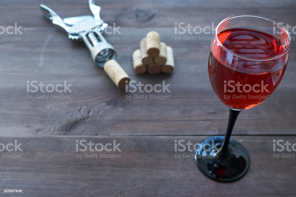 cup of pink wine on table with corkscrew aside stock photo