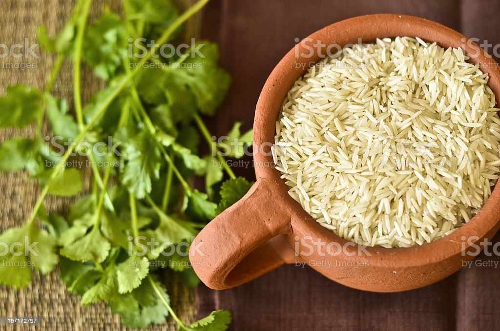Cup of rice and cilantro leaves on a table royalty-free stock photo