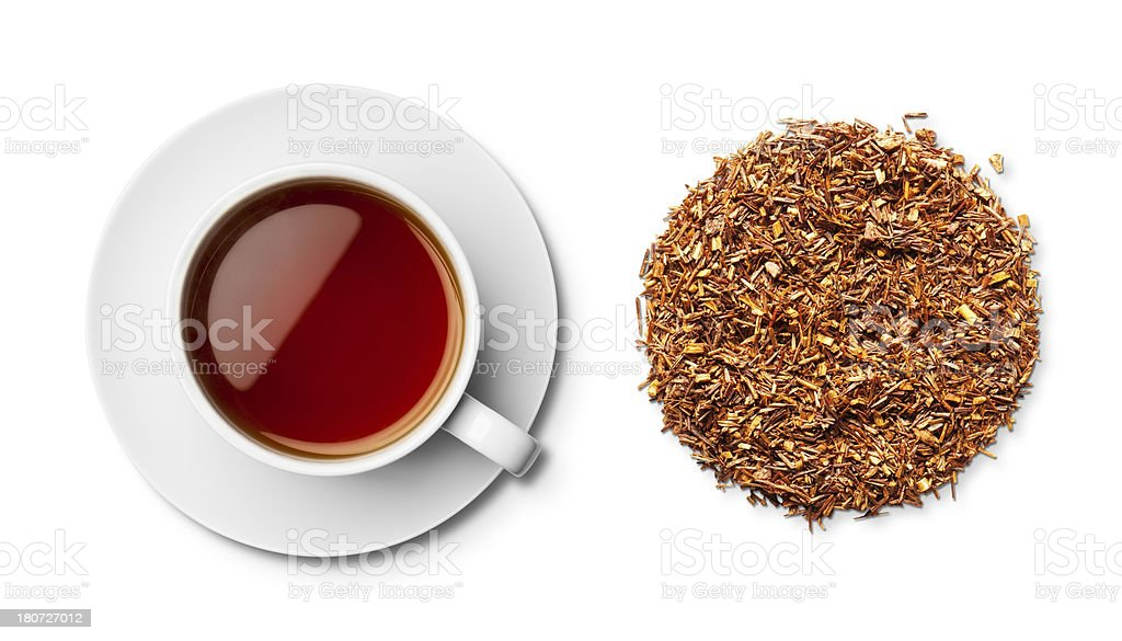 Cup of rooibos red chai tea and leaves overhead stock photo