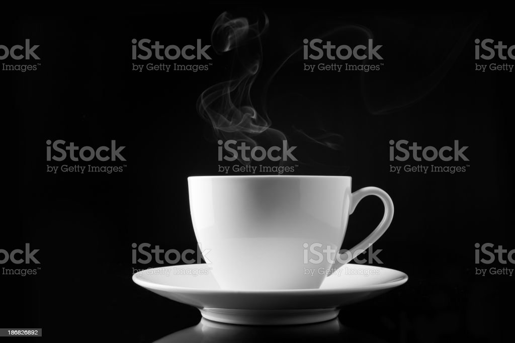 A cup of smoking hot coffee on a black background stock photo