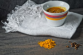 cup of steaming hot soup with spices on cotton embroidered
