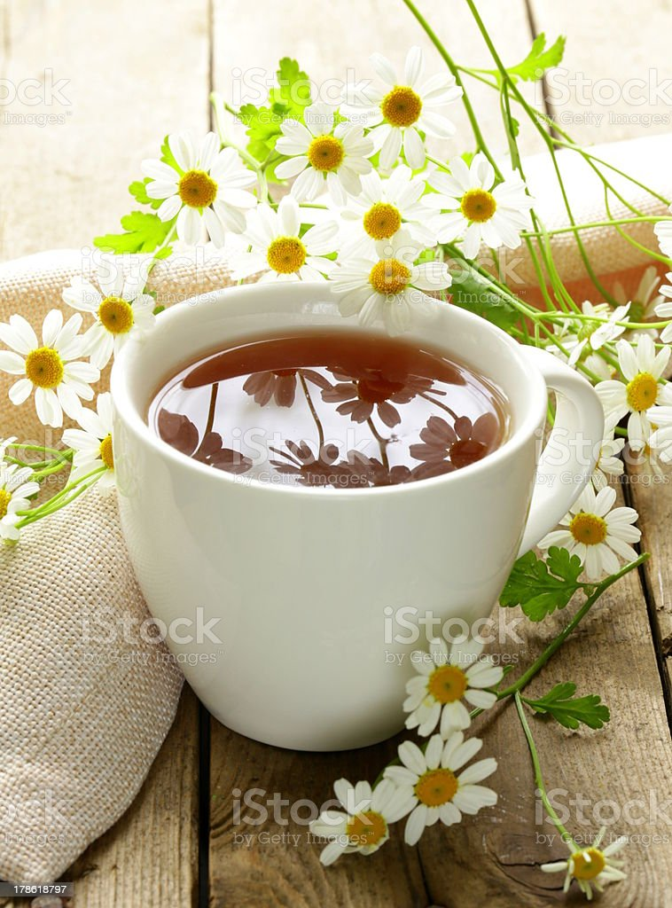 cup of tea and chamomile flowers on a wooden table royalty-free stock photo