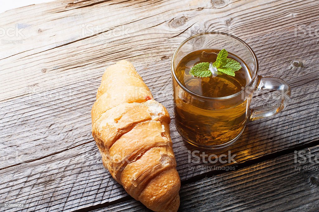 Cup of tea and croissant on wooden table. stock photo