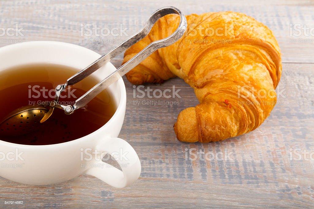 Taza de té y un croissant foto de stock libre de derechos