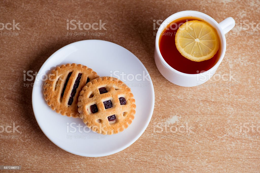 Cup of tea and lemon, cookies with jam in saucer stock photo