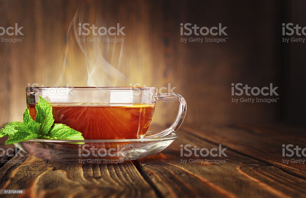 Cup of tea and mint on a wooden background stock photo