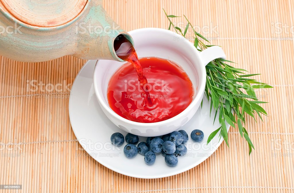 Cup of tea being poured from a teapot with side of berries royalty-free stock photo