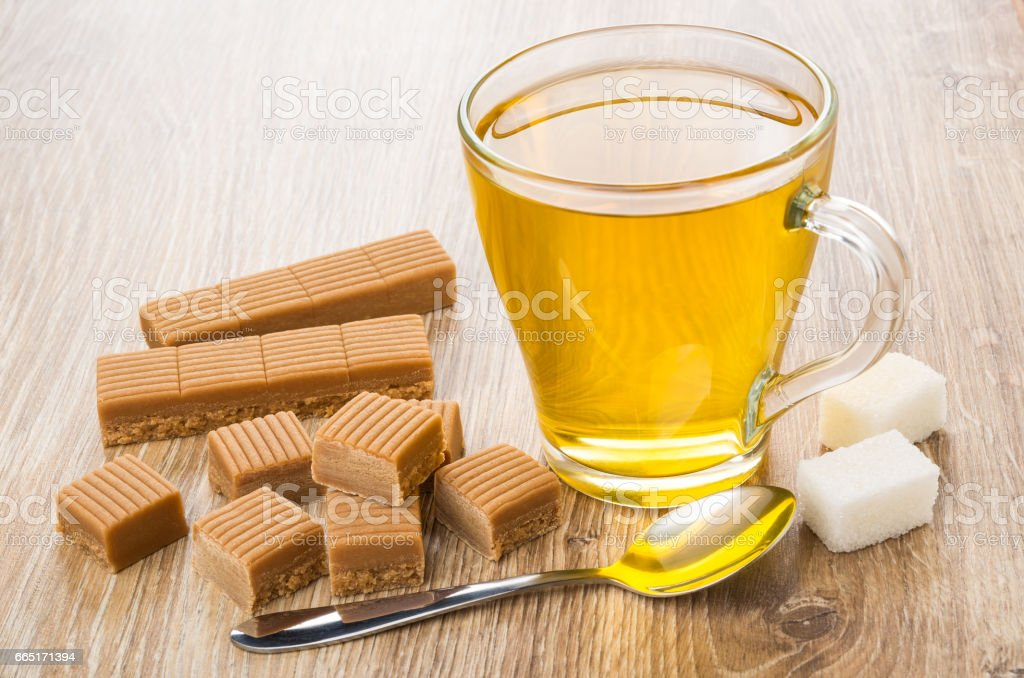 Cup of tea, creamy toffee, lumpy sugar and spoon stock photo
