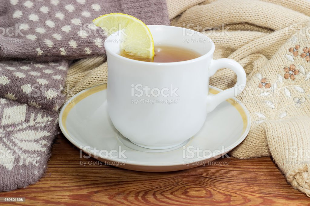 Cup of tea on background of woolen mittens and scarf stock photo
