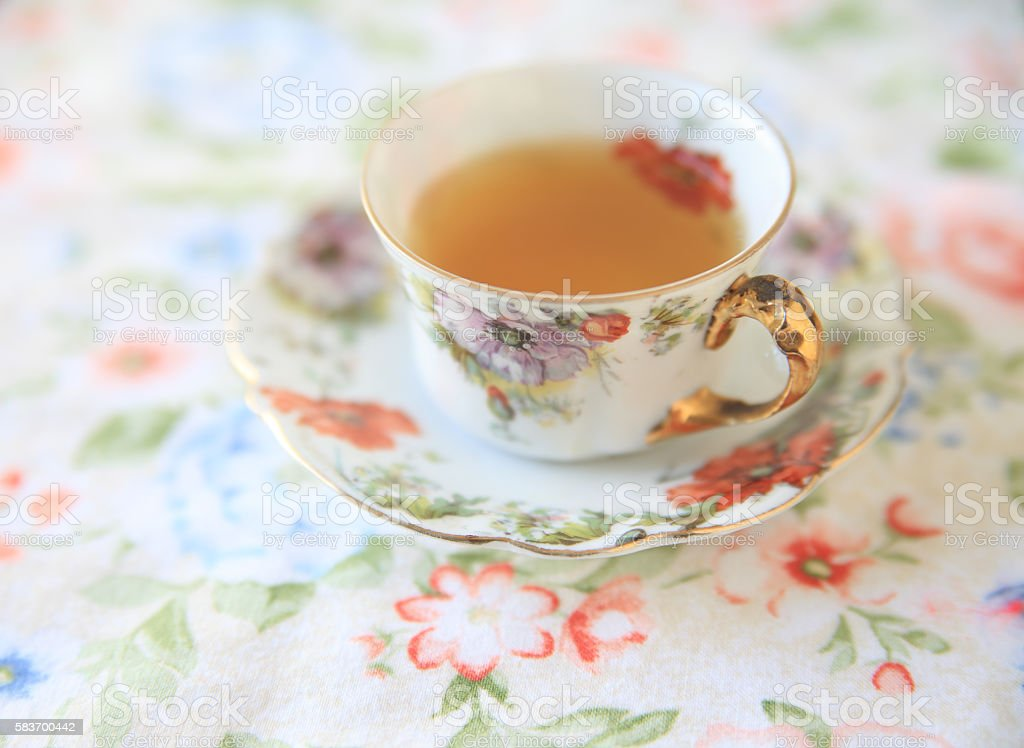 Cup of tea on flower print fabric stock photo
