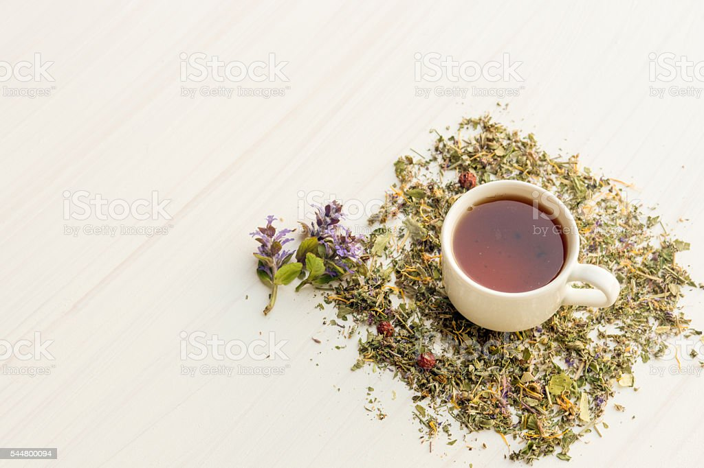Cup of tea on table with herbs stock photo