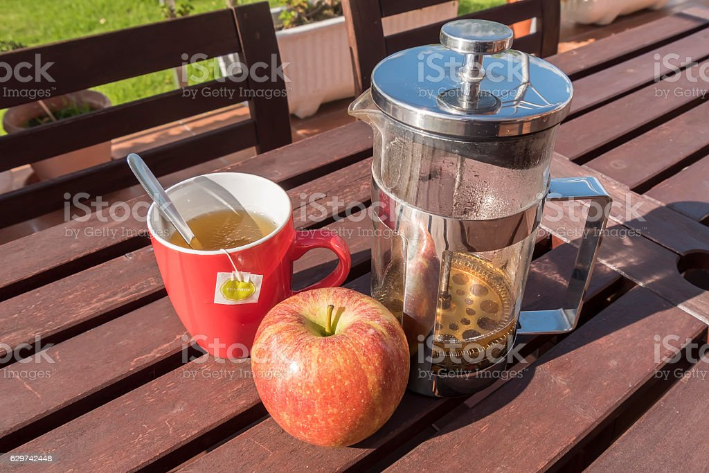Cup of tea with apple, breakfast in the garden stock photo
