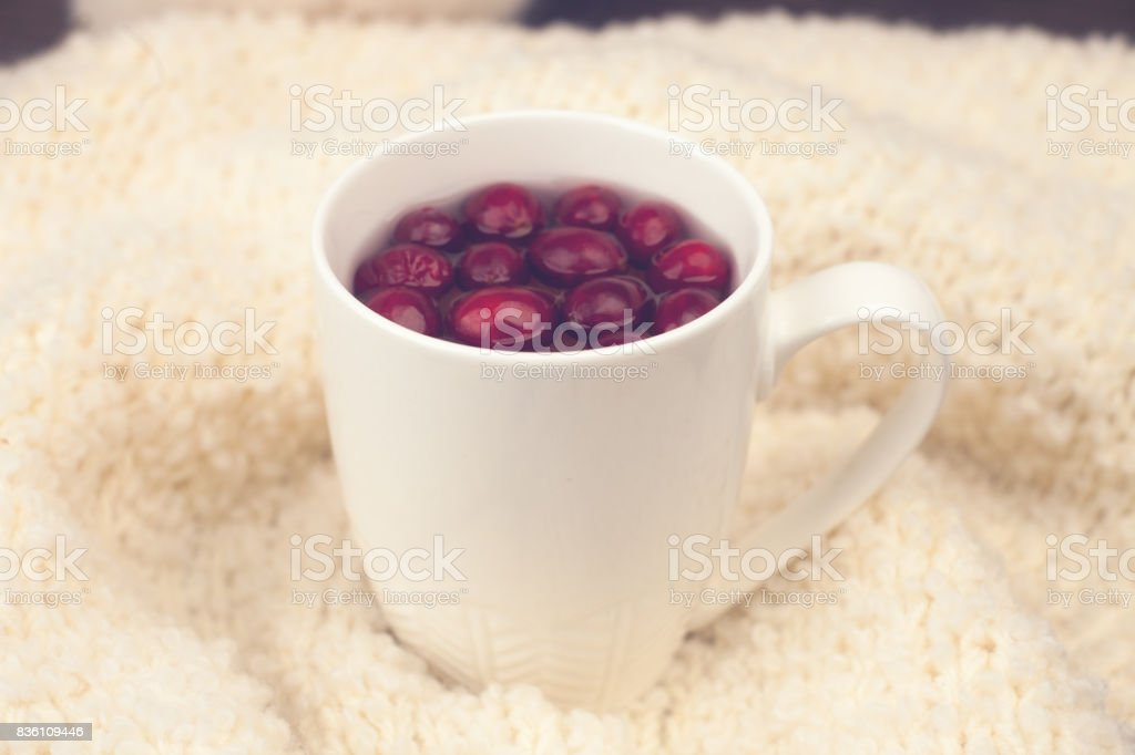 Cup of tea with cranberries, warf soft background - the concept of seasonal respiratory diseases, treatment of colds stock photo