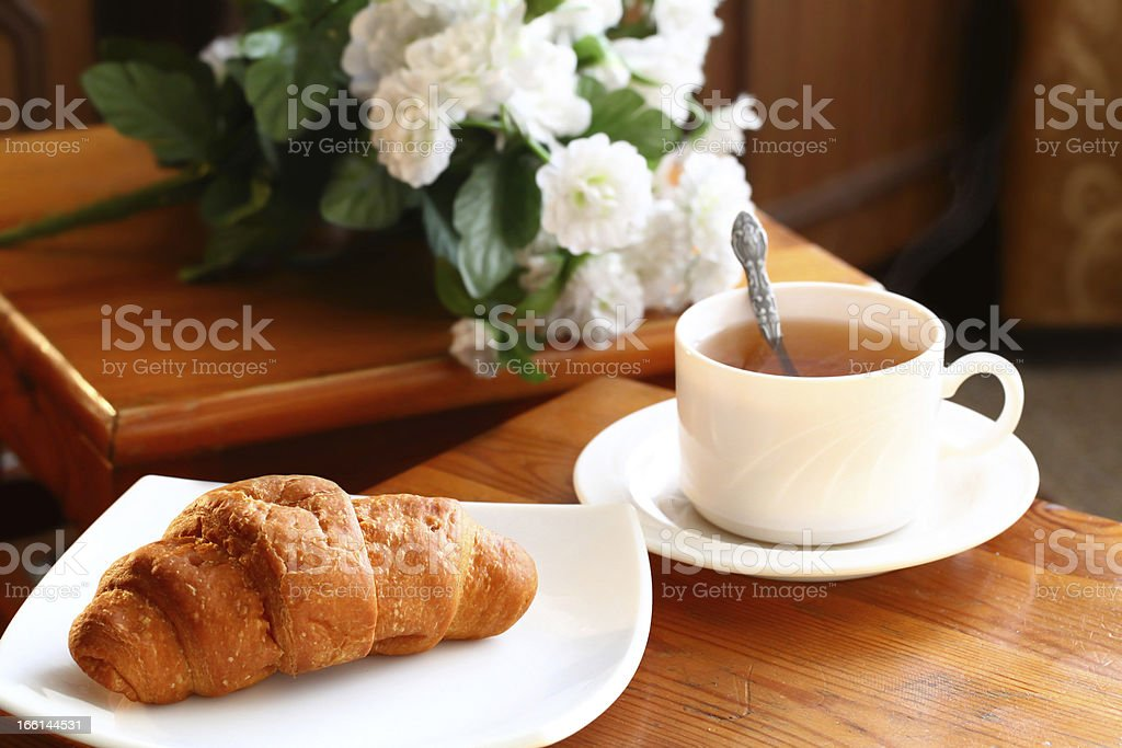 Cup of tea with french croissant stock photo