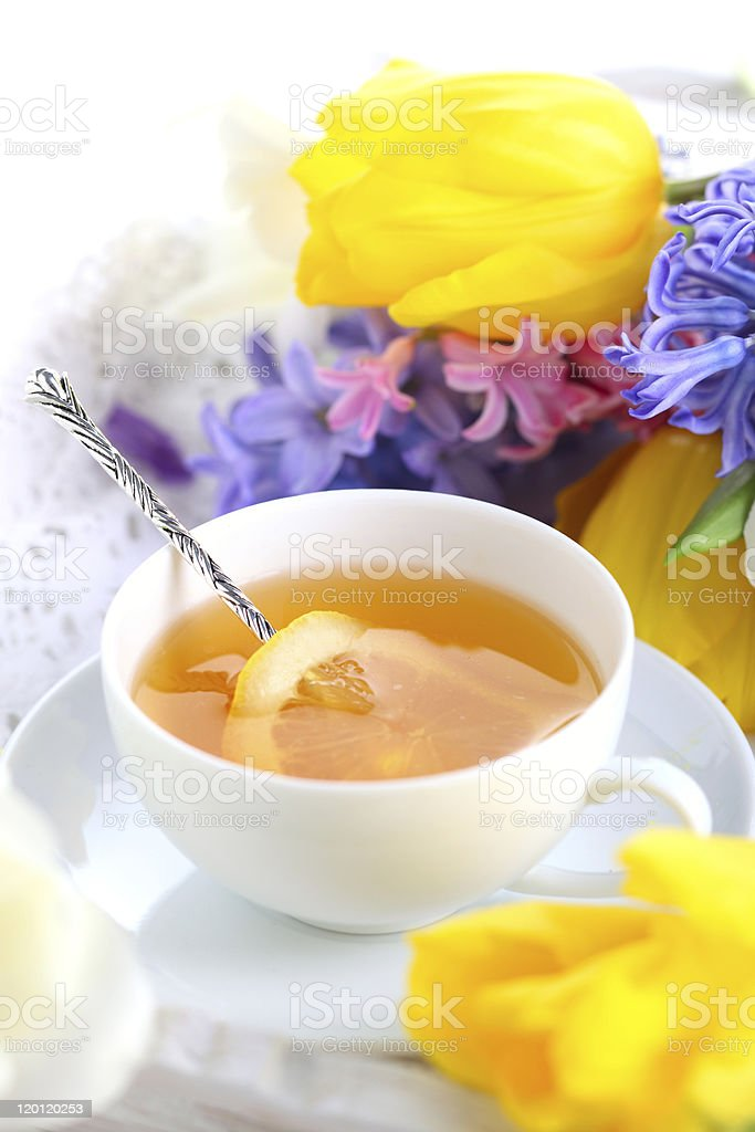 Cup of tea with lemon and spring flowers close up stock photo