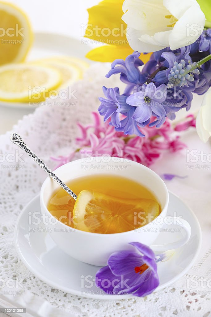 Cup of tea with lemon and spring flowers stock photo