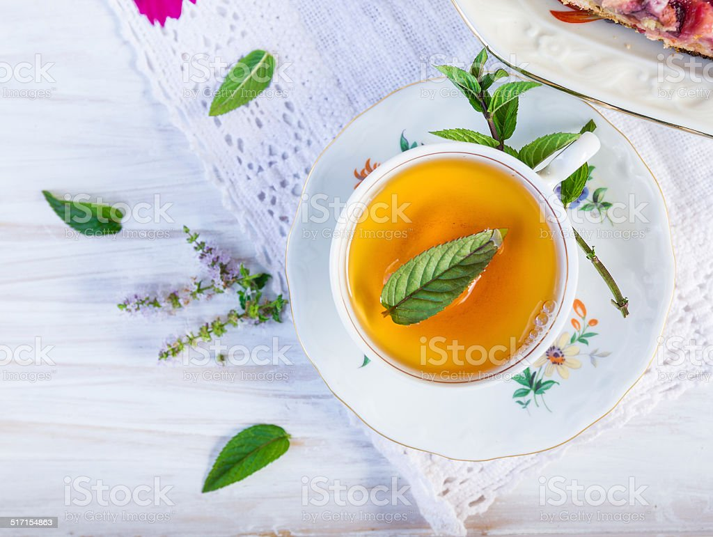 Cup of tea with peppermint on  lacy napkin. stock photo