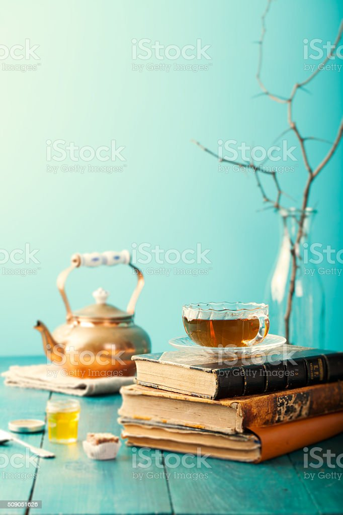 Cup of tea with teapot and vintage books stock photo