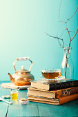 Cup of tea with teapot and vintage books