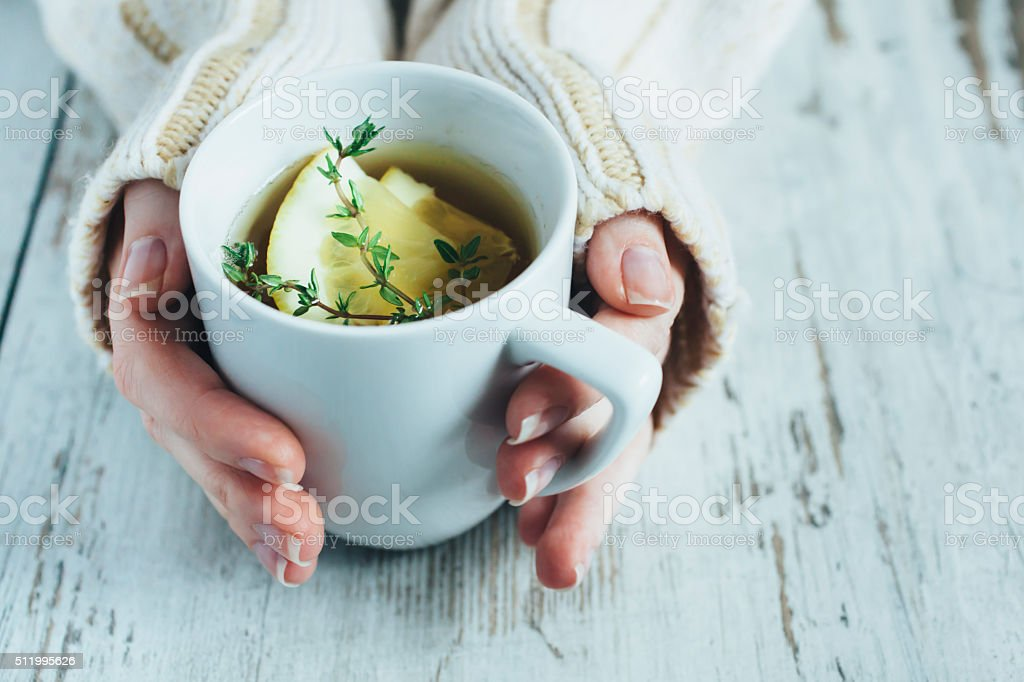 Cup of tea with thyme herb and lemon slices stock photo