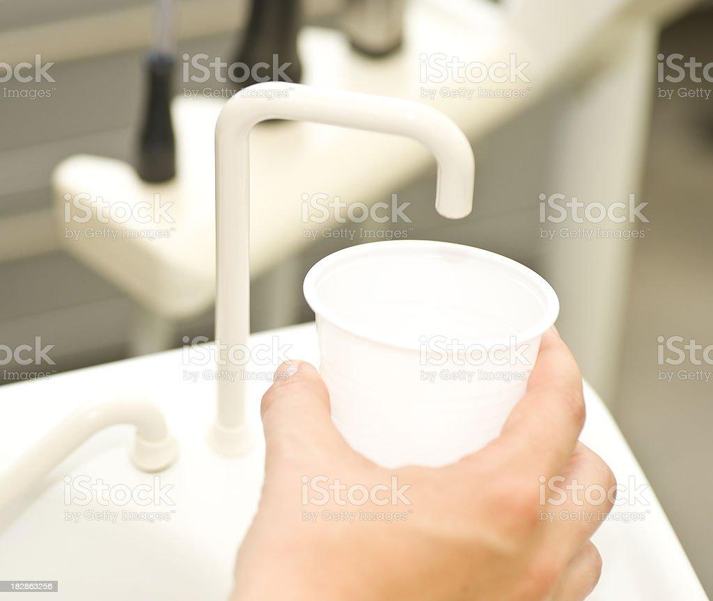 cup of water at dentist - spülen beim zahnarzt stock photo