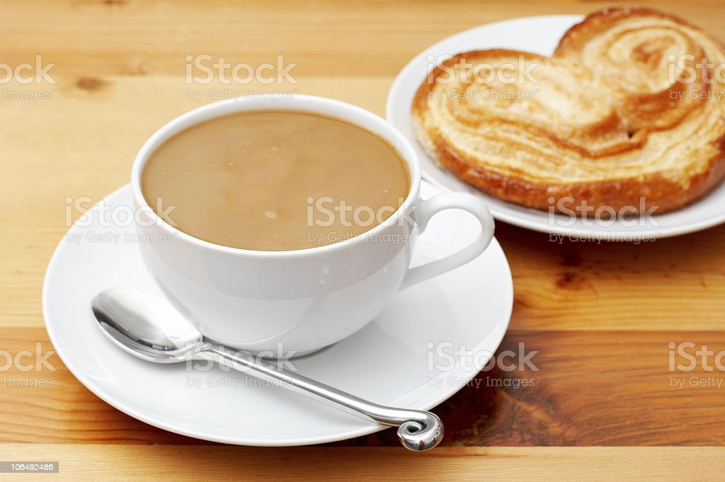 Cup of white coffee beside a palmera pastry on a plate stock photo