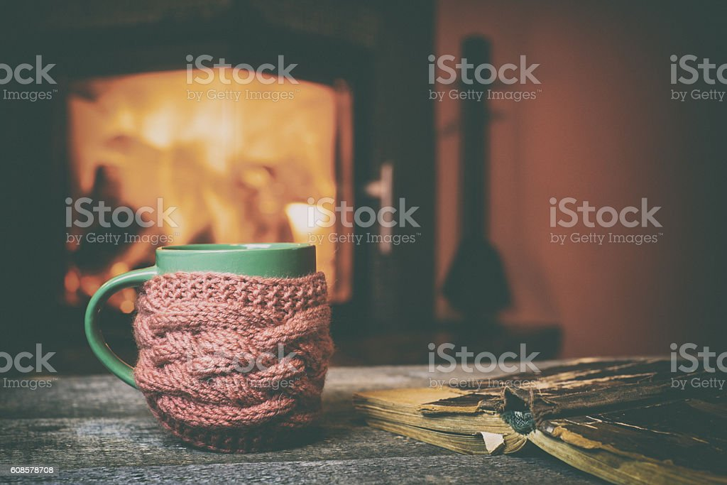 Cup, old book, glasses on vintage wood near fireplace stock photo