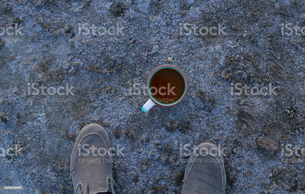 Cup with a drink and shoes on salt soil shore stock photo