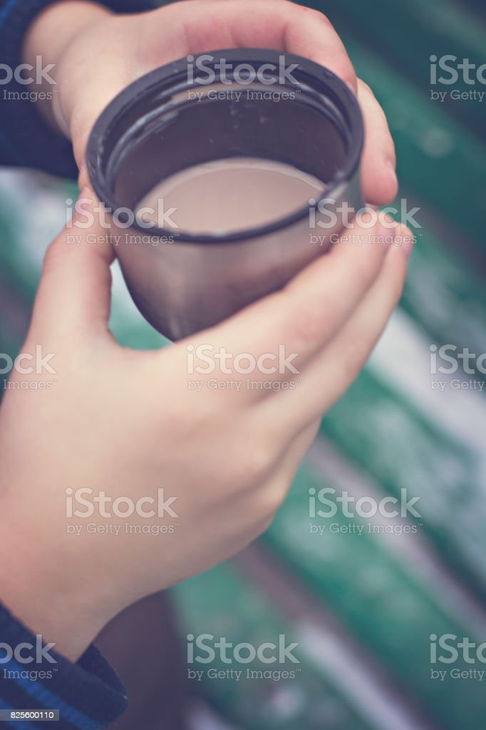 A cup with a hot drink in the children's hands stock photo
