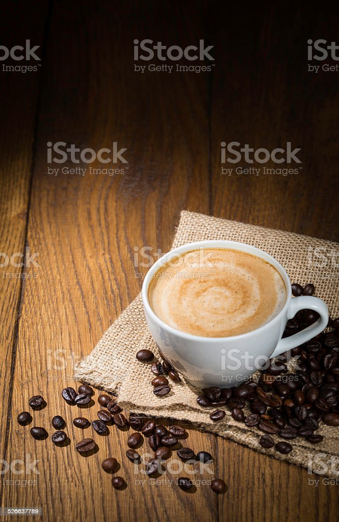 cup with cappuccino with coffee beans on wooden table stock photo