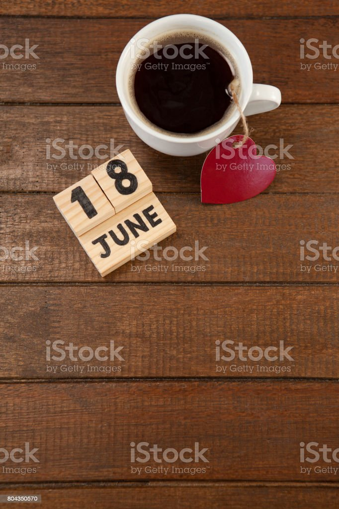 Cup with heart decoration and date arranged on wooden plank stock photo