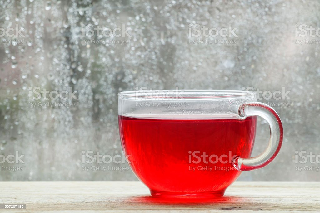 Cup with hot red tea in front of a window stock photo