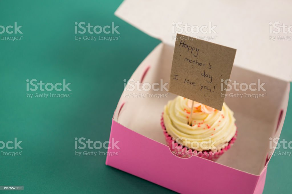 Cupcake against with happy mother day card green background stock photo
