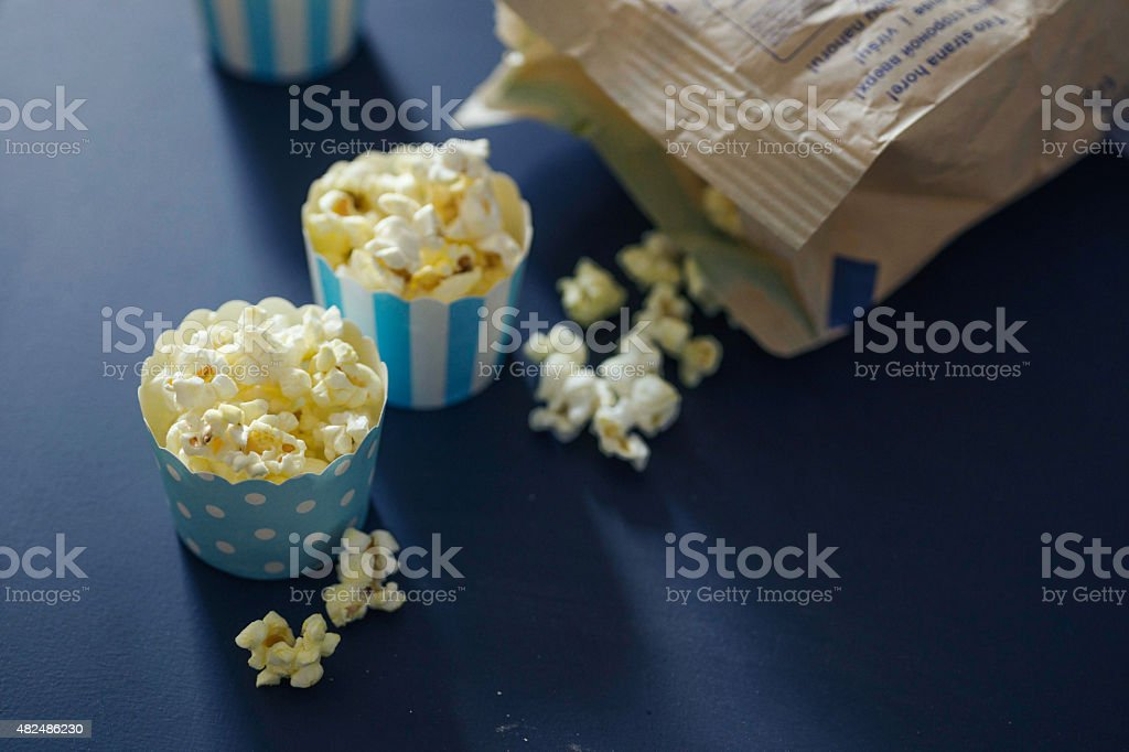 Cupcake cases filled with salty caramel popcorn on chalkboard background stock photo