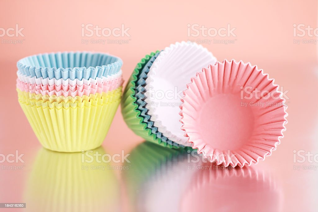 Cupcake liners in pastel tones on pink background stock photo